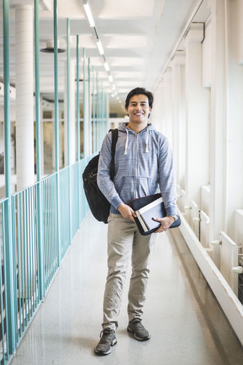 Portrait of young man standing in corridor of building