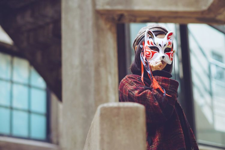 Woman Wearing Mask Against Window