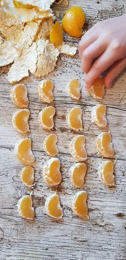 Cropped hand arranging orange fruits on wooden table