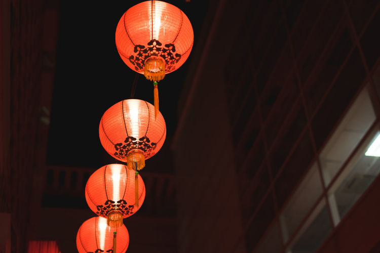 Low angle view of illuminated lantern hanging against ceiling