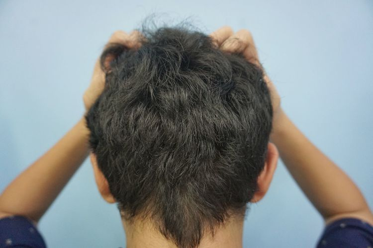 Rear view of boy with hands in hair at home