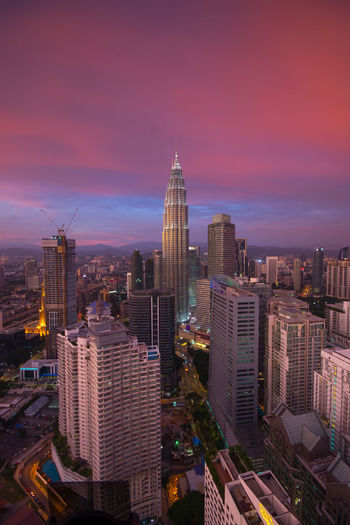 Petronas towers and buildings in city against cloudy sky during sunset