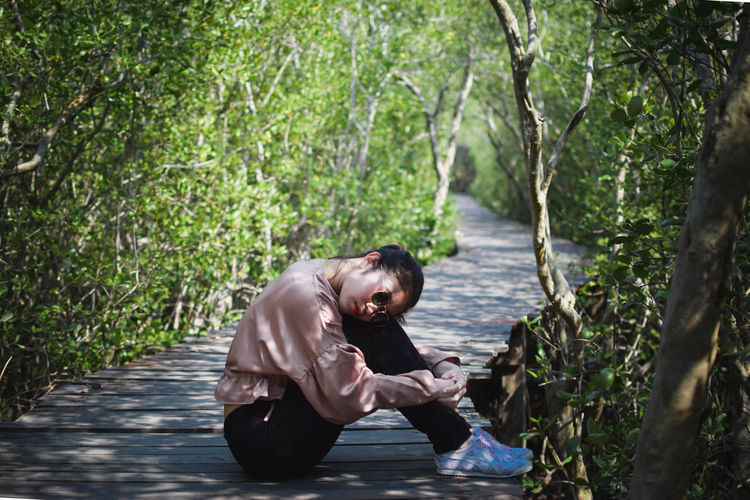 Side view of young man sitting on land in forest