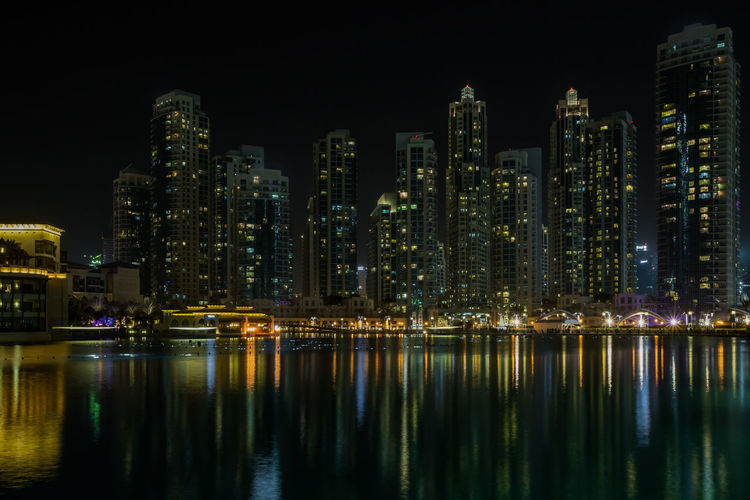 Illuminated city by buildings against sky at night