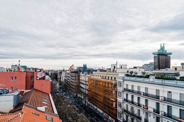 High angle view of road amidst buildings against cloudy sky