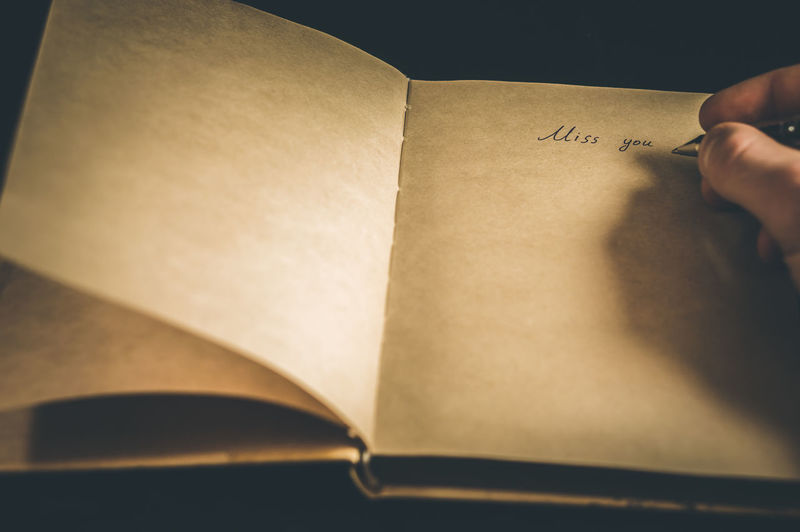 Cropped Hand Writing On Book