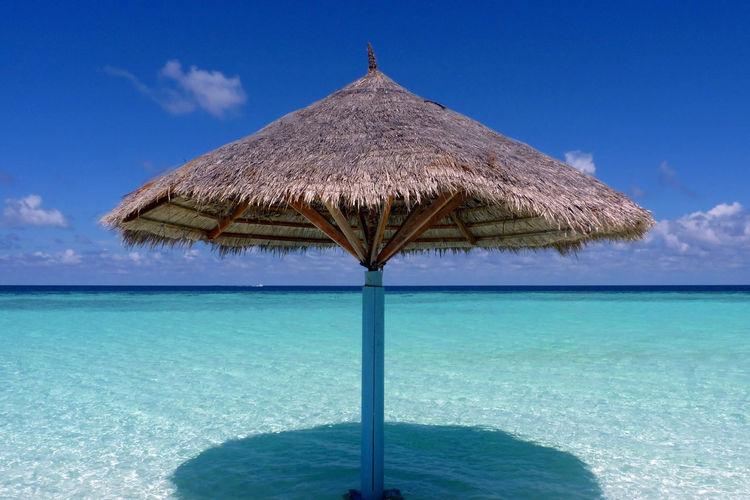 Lifeguard hut on sea against blue sky