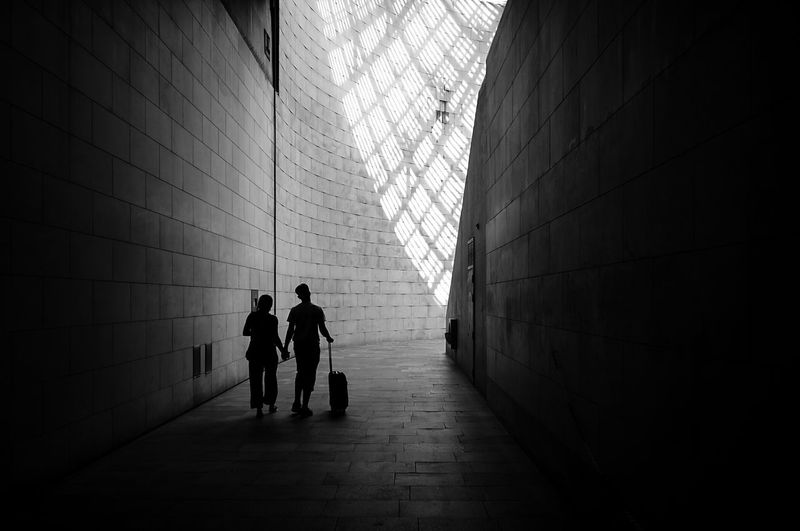 Men walking in corridor of building