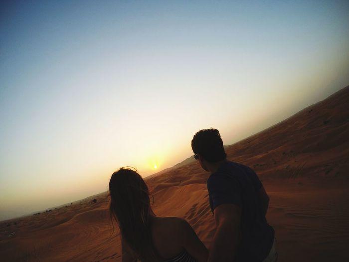 Tilt image of couple standing on desert against sky during sunset