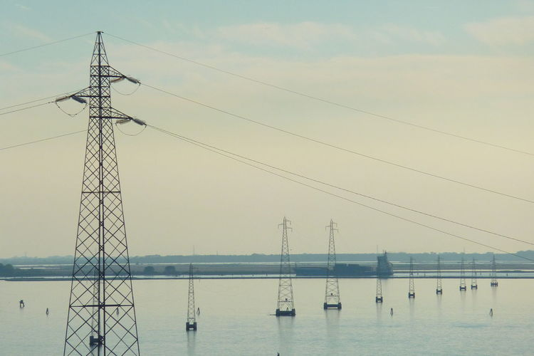 Electricity Pylons Over Sea Against Sky