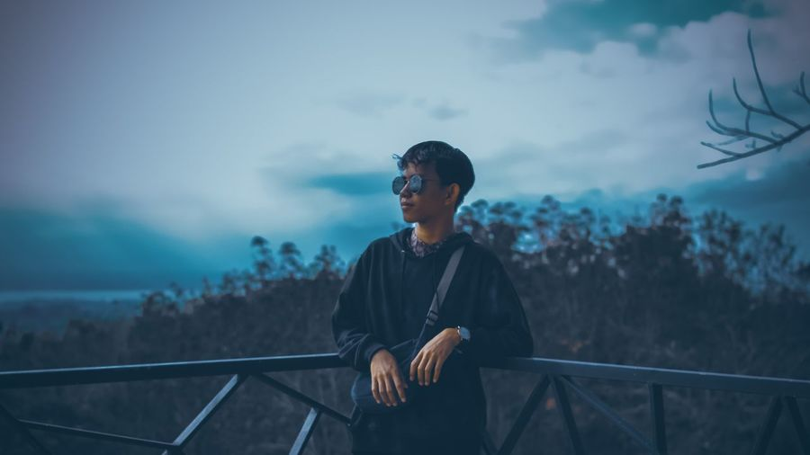 Teenage boy wearing sunglasses standing by railing against sky at dusk