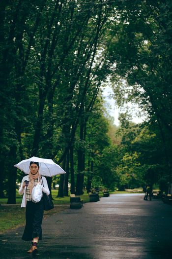 White umbrella. City Life City Park City Street Rain Walking Around Woman Day Front View Greenery Leisure Activity Lifestyles One Person Outdoors People Rainy Rainy Day Real People Street Photography Streetphotography Umbrella Walking White Umbrella Young Women