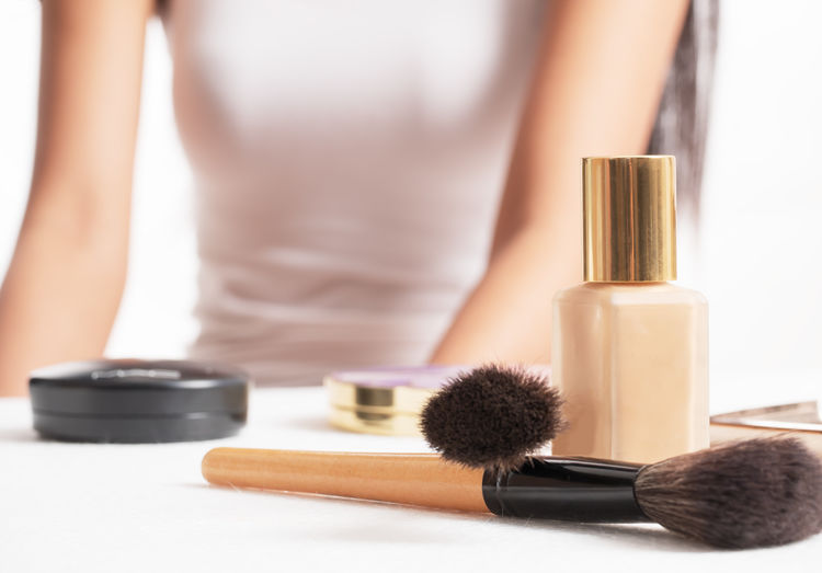 Midsection of woman with beauty products