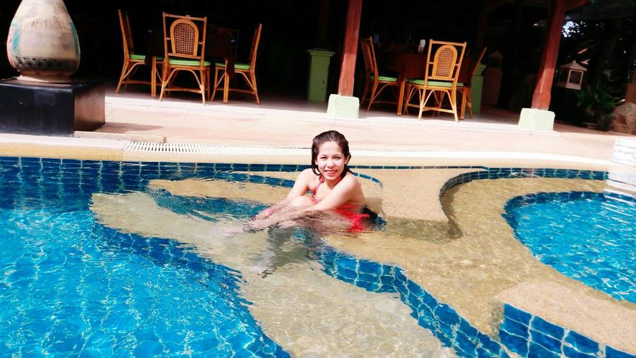 Portrait of smiling young woman sitting in swimming pool