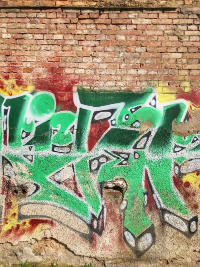 Wall Brick Wall Wall - Building Feature Brick Graffiti Green Color No People Art And Craft Built Structure Creativity Multi Colored Architecture Day Street Art Close-up Mural Outdoors Representation Full Frame Text Turquoise Colored