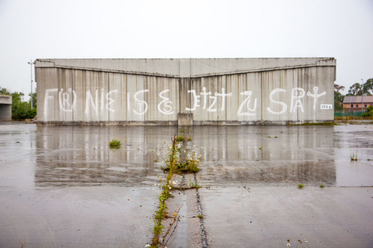 Text on wall against clear sky