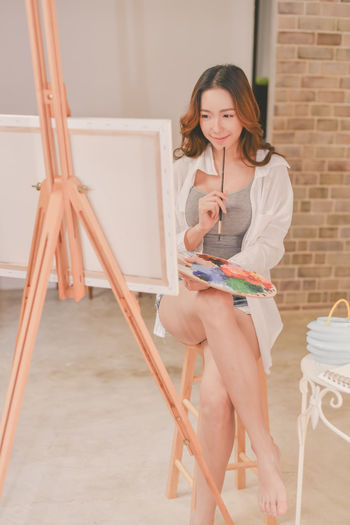 Young painter painting at home
