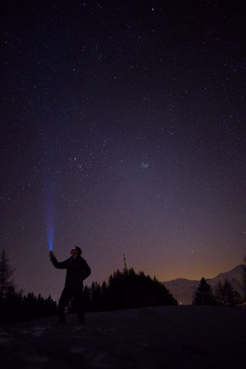 Silhouette man holding illuminated flashlight towards star field sky during night