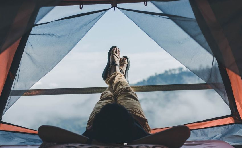 Man lying in tent with mountains in background