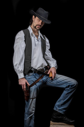 Handsome young man. This is an American cowboy. A vow to a white shirt, brown waistcoat and blue jeans. Black shoes on the feet. Carries a shtyapa, on a belt two pistols. The hair is of medium length; on the face is a beard and mustache. Authentic photo. Culture of America. Cowboy Wild West America American Gun National Authentic Moments Lifestyles Lifestyle One Person Candid Authentic Black Background Three Quarter Length Hat Clothing Young Men Men Casual Clothing Young Adult Front View Males  Standing Adult Jeans