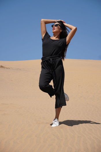 Full length of young woman standing on desert against clear sky