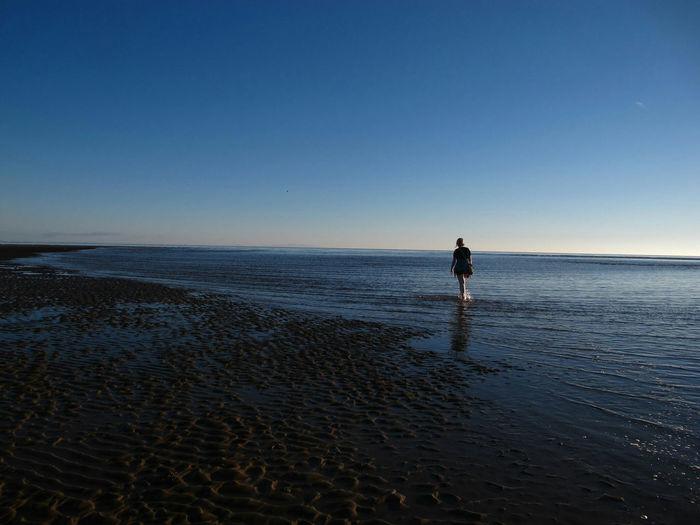 Man standing on calm beach against clear blue sky