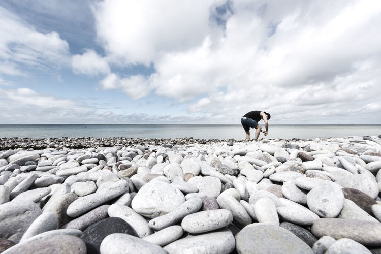 Man collecting pebbles on shore against sky