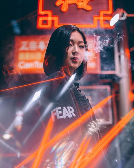 Young woman with illuminated light painting at night
