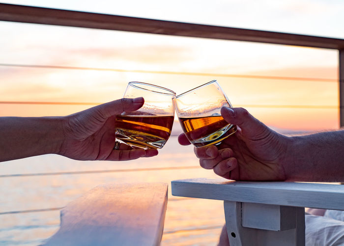 Friends Toasting Whiskey Against Sea During Sunset