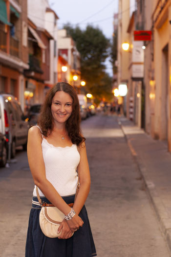 Portrait of smiling woman standing in city