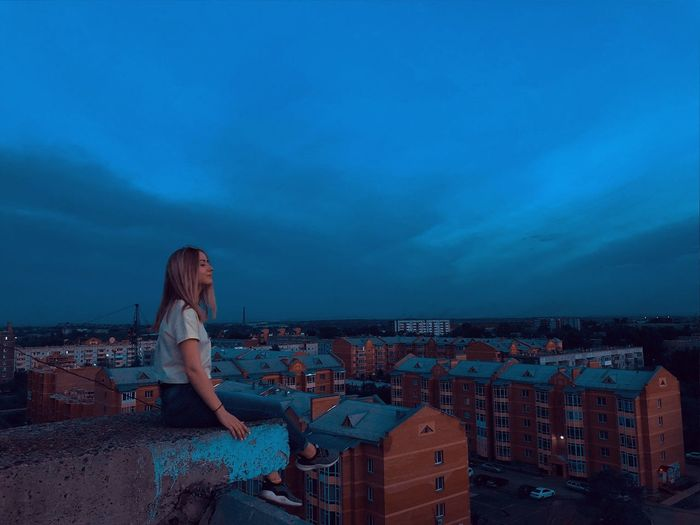 Woman sitting on terrace while looking townscape at dusk