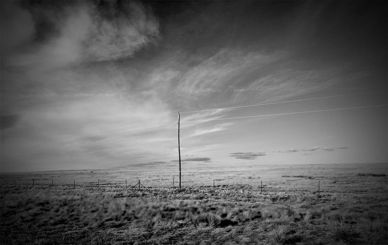 """""""Lone Pole Standing"""" There was just something that spoke to me in this scene. I was driving between Roswell and Corona, New Mexico. It was open range, mystic clouds above. I actually shot it while driving, through the window. It's not perfect, blurred in spots but it spoke to me in the loneliness of the rural power pole and its wires going horizontally into nothingness against the backdrop of the plains and finger painted sky. Plains Powerpole Openrange Blackandwhite Black And White Blackandwhite Photography Black And White Photography Rural Ruralroad"""