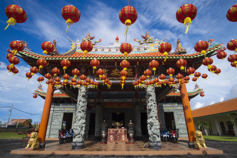Benoa, Bali, Indonesia - January 28, 2017 : People praying and wishing a happy chinese new year on vihara satya dharma. Architectural Column Architecture Belief Building Building Exterior Built Structure Chinese Lantern Cloud - Sky Day Entrance Façade Low Angle View Nature No People Ornate Outdoors Place Of Worship Religion Sky Spirituality