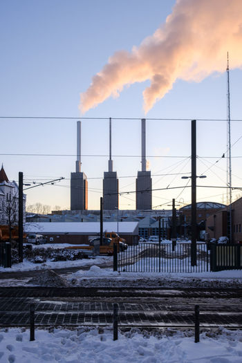 Smoke emitting from snow covered factory against sky