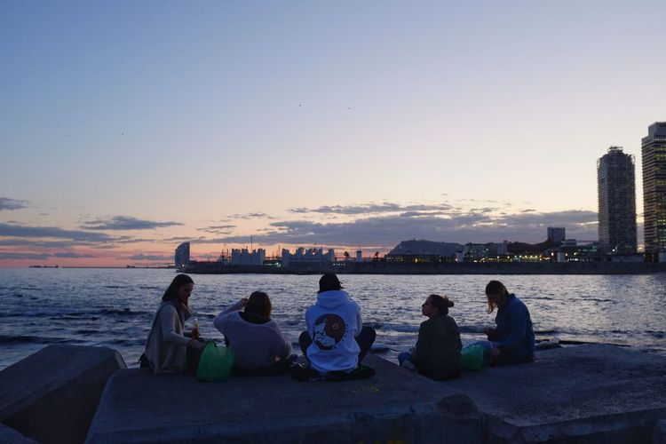 People sitting by sea against clear sky during sunset