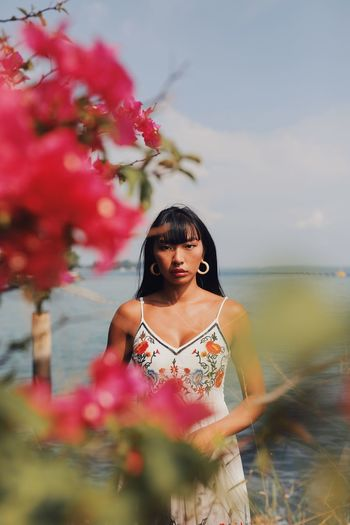 Portrait of woman seen through flowering plant standing at beach against sky