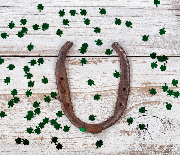 Close up view of a rusty horseshoe for St Patrick day with shiny clovers on weathered white wooden boards Clover Holiday Horseshoe Luck St Patrick's Day Wood Irish St Patrick