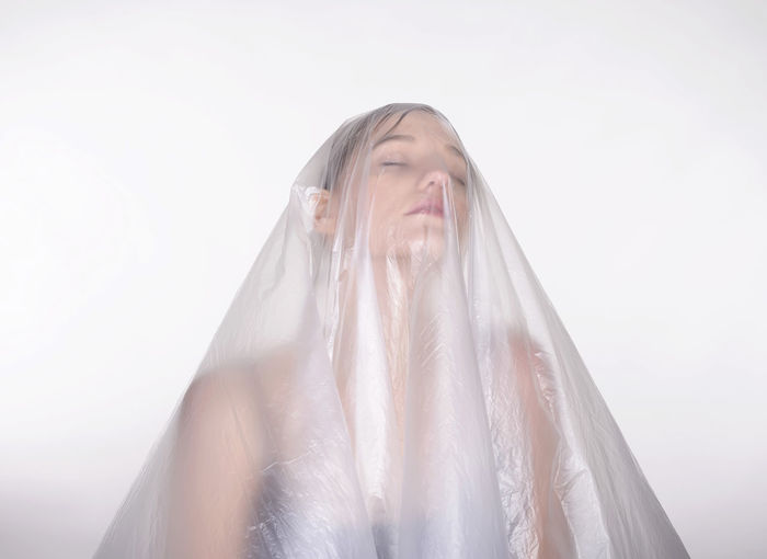 Close-up of woman covered in plastic against white background