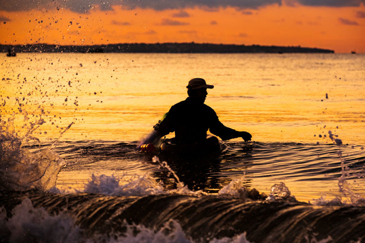 A fisherman doing fishing in the sea. Real People Sunset Water Sea Sky One Person Silhouette Leisure Activity Nature Orange Color Lifestyles Men Beauty In Nature Horizon Over Water Horizon Waterfront Scenics - Nature Outdoors Fishing Golden Sunrise Wave Ocean Fisherman Outline Shadow