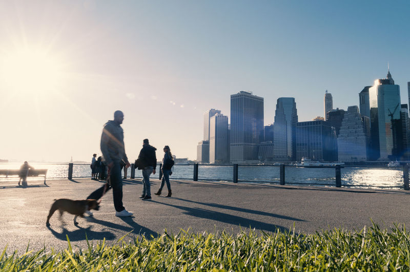 Silhouetted people on the waterfront with lower manhattan skyline  the east river in late afternoon.