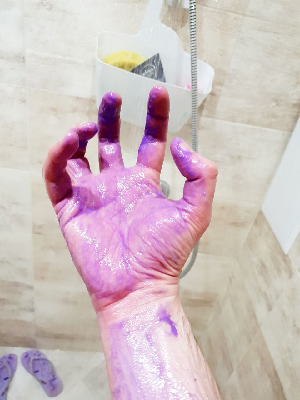 human hand, hand, human body part, real people, one person, indoors, pink color, body part, high angle view, unrecognizable person, lifestyles, finger, human finger, personal perspective, close-up, paint, messy, multi colored, flooring, holi, nail, purple