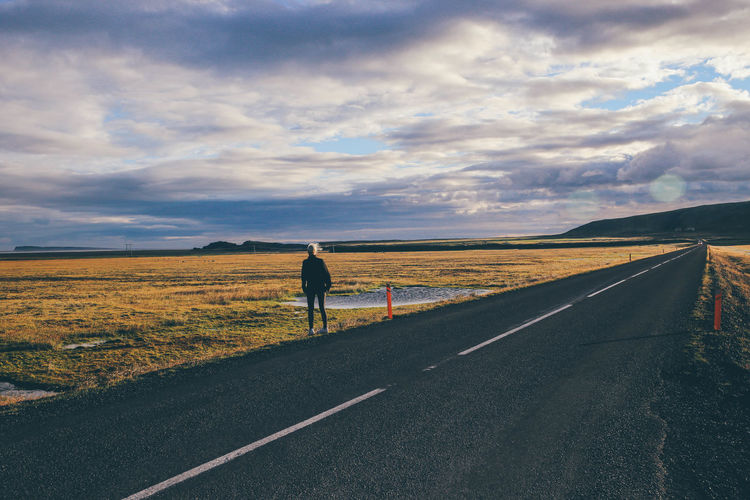 Rear View Of A Person At The Edge Of A Country Road