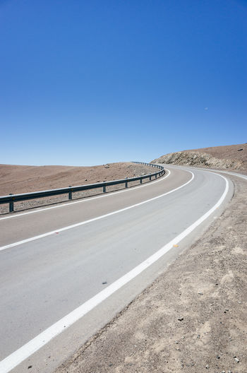 Empty Road In Desert Against Clear Blue Sky