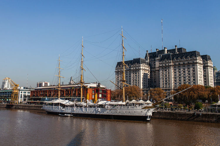 Sailboats in river by buildings against clear sky