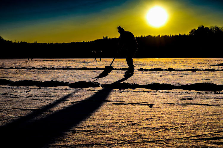 Clearing the Playground II Ice Winter Working Beauty In Nature Cold Temperature Icehockey Leisure Activity Nature One Man Only One Person Real People Shadow Silhouette Sun Sunlight Sunset Tranquility