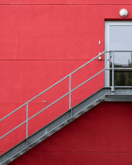 Low angle view of building against red wall