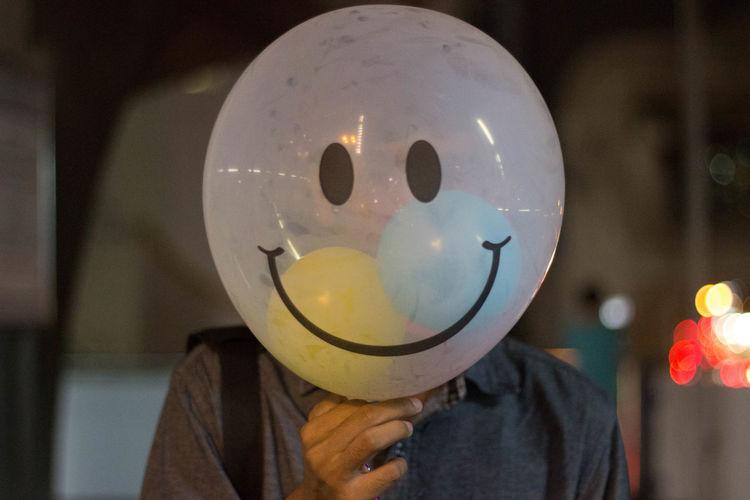 Man holding balloon at home
