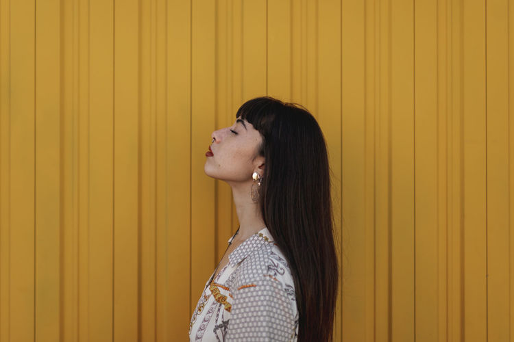 Woman looking away against yellow wall
