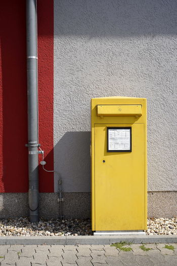 Yellow mailbox on wall of building