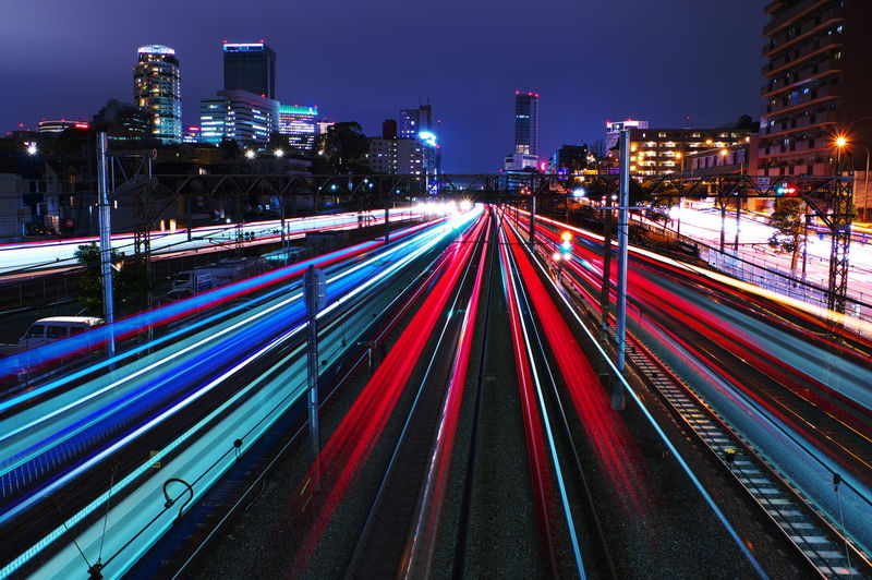 Light trails on railroad tracks amidst buildings in city at night